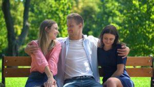 handsome-men-resting-bench-park-hugging-two-attractive-females-ladies-man