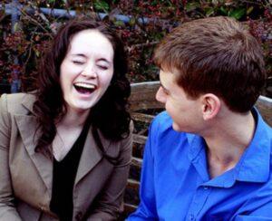 A woman laughing at a man's jokes