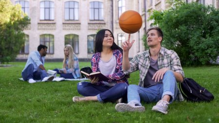 A guy playing with a ball around a girl