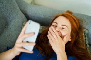A woman laughing over a text message