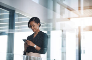 Shot of a young businesswoman using a cellphone in an office