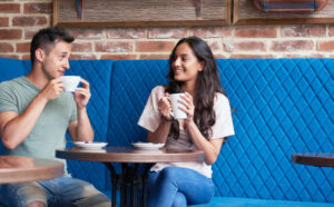 A beautiful woman taking coffee with a man on their first date.