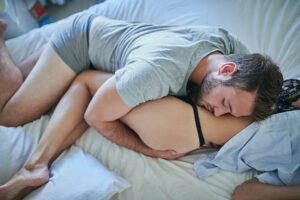 Shot of a young man holding on to his girlfriend in bed