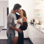Shot of a young couple making out in the kitchen